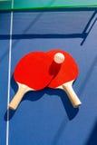 Ping-pong de los tenis de mesa dos paletas y bola blanca Fotos de archivo libres de regalías