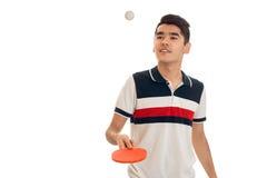 Ping-pong di pratica del giovane sportivo felice del brunett isolato su fondo bianco Fotografia Stock