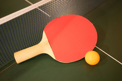 Ping Pong. A ping pong paddle and ball on a table Royalty Free Stock Photo