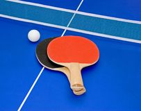 Ping pong paddles. Red and black ping pong paddles and a white ball stock image