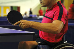 Ping pong player. Image of a disabled man in wheelchair playing table tennis. Live image from an international tennis table competition for persons with Stock Image