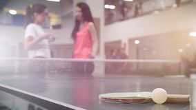 Ping-pong que juega en un club de deporte Amigos de las mujeres jovenes que hablan en el fondo La estafa y poca bola en metrajes