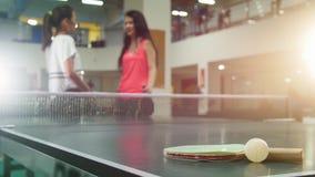 Ping-pong que juega en un club de deporte Mujeres jovenes que hablan en el fondo La estafa y poca bola en el primero plano almacen de metraje de vídeo