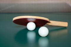 Ping-pong racket and a  two balls on a green table. ping-pong net royalty free stock image