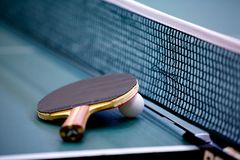 Ping Pong. Table tennis or ping pong racket with a white ball on a ping pong table before the net Royalty Free Stock Photo