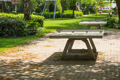 Ping pong tables in a public park playground. Outdoors in a city park playground are two cement ping pong tables surrounded by grass and trees on a spring day Stock Images