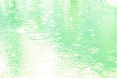 Pingos de chuva em uma po?a em um dia chuvoso Tom azul macio fotografia de stock