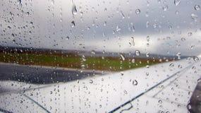 Pingos de chuva na janela do avião pela pista de decolagem Imagem de Stock Royalty Free
