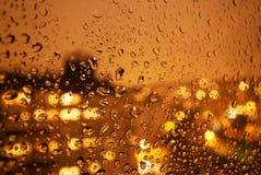 Pingos de chuva na janela na noite na cidade Fotografia de Stock Royalty Free