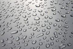 Pingos de chuva na superfície da prata Imagens de Stock Royalty Free