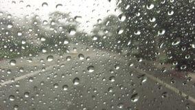 Pingos de chuva no para-brisa ao conduzir abaixo da estrada video estoque