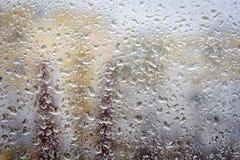 Pingos de chuva no vidro, opinião do fundo da janela das construções fora de foco foto de stock