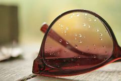 Pingos de chuva nos óculos de sol da lente fotografia de stock
