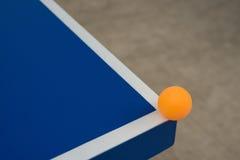 Pingpong ball hits the corner of blue pingpong table Stock Photo