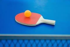 Pingpong racket and ball and net on blue pingpong table Royalty Free Stock Photo