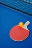 Pingpong racket and ball and net on a blue pingpong table Royalty Free Stock Image