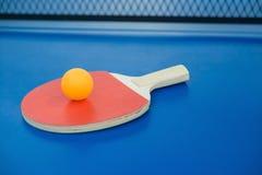 Pingpong racket and ball on a pingpong table Stock Image