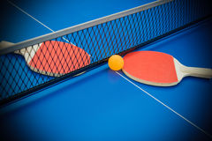 Pingpong rackets and ball highlighted on blue pingpong table Stock Photography