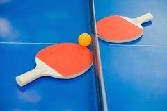 Pingpong rackets and ball and net on blue pingpong table Stock Photo