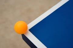 Pingpongball schlägt die Ecke einer Pingpongtabelle Stockbild