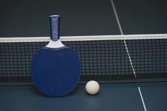 Pingpongrackets en bal en netto op een blauwe pingponglijst stock afbeeldingen