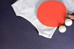 Pingpongrackets, sportenoverhemd en ballen op een donkere achtergrond Stock Afbeelding