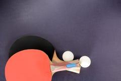 Pingpongrackets, sportenoverhemd en ballen op een donkere achtergrond Stock Foto's