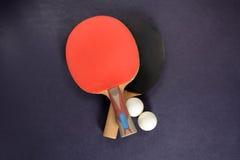 Pingpongrackets, sportenoverhemd en ballen op een donkere achtergrond Royalty-vrije Stock Afbeeldingen