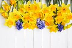 Pingstliljablommor och hyacinter över vit träbakgrund Royaltyfri Bild