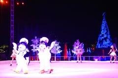 Pinguine und Mädchen, die auf Eis am Weihnachtszeigung im internationalen Antriebsbereich eislaufen lizenzfreie stockfotografie