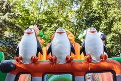 Pinguins infláveis de uns desenhos animados em uma atração das crianças fotografia de stock royalty free
