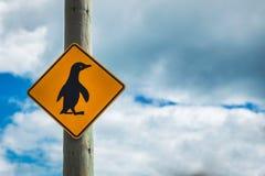 Pinguins que cruzam o sinal com fundo Nova Zelândia do céu nebuloso fotografia de stock royalty free