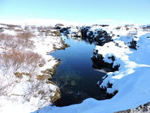 Pingvellir National Park, Iceland - clear natural blue water, reflection, snow. Royalty Free Stock Photo