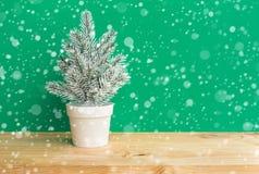 Pinheiro bonito no potenciômetro com queda de neve no fundo de madeira da tabela da barra Feliz Natal fotografia de stock