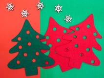 pinheiros de feltro do vermelho e do verde e alguns flocos de neve de madeira Fotos de Stock