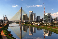 Pinheiros River and Bridge Sao Paulo Brazil. A large fork style construction holding yellow cables of a bridge, a large red and white television antenna and the Royalty Free Stock Image