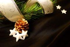 Pinho do Natal na fita com estrelas e cone do pinho Fotografia de Stock Royalty Free