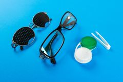 Pinhole glasses, lenses with container and glasses for sight. Medical concept. A set of accessories for sight. Top view Stock Photography