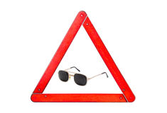 Pinhole glasses among warning triangle on a light background Royalty Free Stock Image
