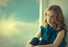 Pining triste, hermoso de la muchacha en la ventana Imagen de archivo libre de regalías