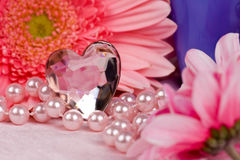Pink. Heart-shaped gem stone with flowers royalty free stock image