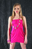 Pink it. Young female fashiom model standing in a pink dress with jewelery against a charcoal back ground Stock Photo