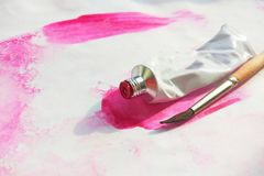 Pink and acrylic paints tubes and hand drawn abstract magenta watercolour drawing picture on white textured paper background. Pink watercolor and acrylic paints royalty free stock photo