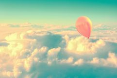 Pink air balloon flying high in the sky above the clouds. Vintage process Royalty Free Stock Photo