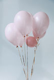 Pink air balloons with golden ribbons. On grey Stock Images