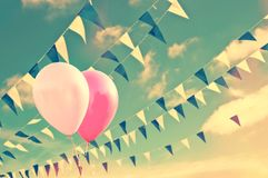 Pink air balloons on sky background with blue and white garlands, summer party concept. Pink air balloons on sky background with blue and white garlands, vintage Royalty Free Stock Image