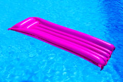 Pink air mattress floating on water of swimming pool Royalty Free Stock Image