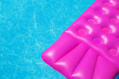 Pink air mattress in swimming pool. Holiday background. Royalty Free Stock Image