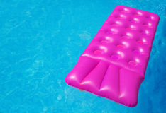 Pink air mattress in swimming pool. Holiday background. Royalty Free Stock Photography