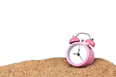 Pink alarm clock on the beach. With white background Royalty Free Stock Image